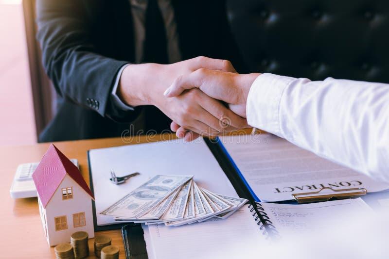 Os agentes e os compradores de vendas da casa trabalham em assinar casas novas e em agitar as mãos imagem de stock