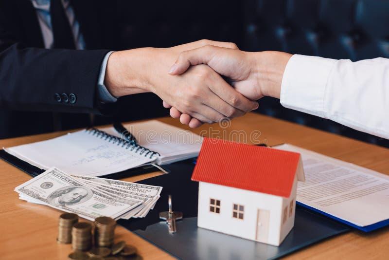 Os agentes e os compradores de vendas da casa trabalham em assinar casas novas e em agitar as mãos imagens de stock royalty free