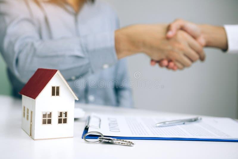 Os agentes e os compradores de vendas da casa trabalham em assinar casas novas e em agitar as mãos foto de stock royalty free