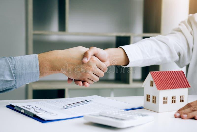 Os agentes e os compradores de vendas da casa trabalham em assinar casas novas e em agitar as mãos fotografia de stock royalty free