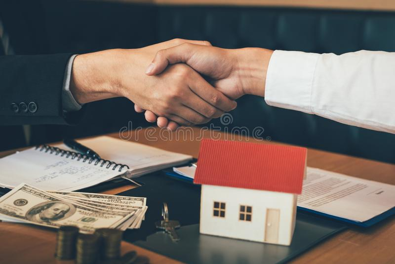 Os agentes e os compradores de vendas da casa trabalham em assinar casas novas e em agitar as m?os imagem de stock royalty free