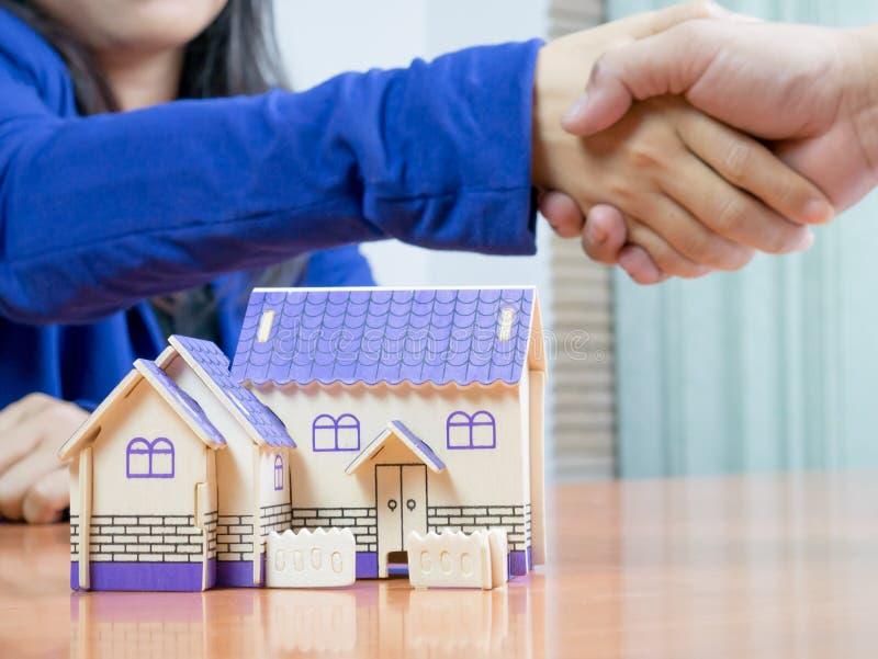 Os agentes imobiliários juntam-se às mãos com compradores imagens de stock