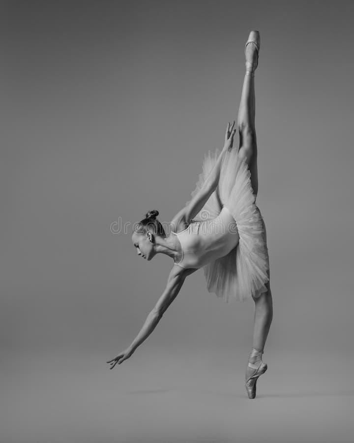 Os alcances da bailarina para o b&w do assoalho imagens de stock