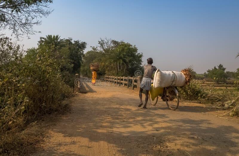 Os aldeões retornam com as colheitas colhidas na extremidade do dia a sua vila rural imagens de stock royalty free
