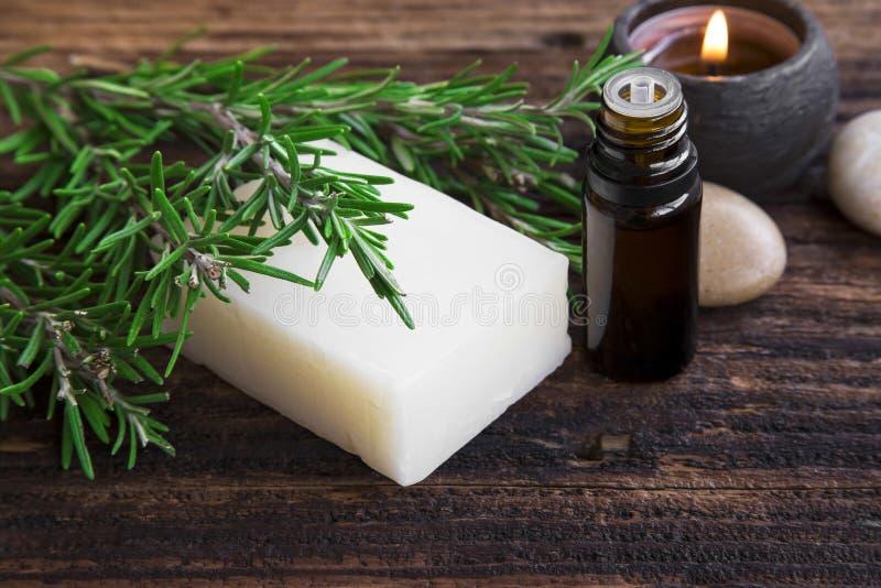 Os alecrins ensaboam e a aromaterapia do óleo essencial com vela na madeira foto de stock