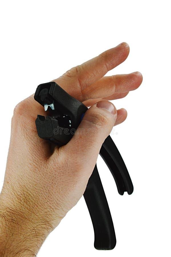 Os alicates plásticos pretos do espadelador do cabo realizaram na mão esquerda do gadgeteer do homem adulto, maxilas visíveis, fu foto de stock