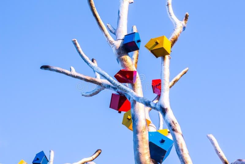 Os alimentadores para pássaros são unidos a uma árvore feita do metal foto de stock royalty free