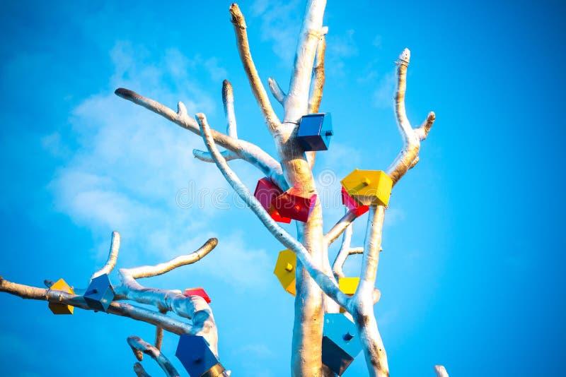 Os alimentadores para pássaros são unidos a uma árvore feita do metal fotografia de stock royalty free