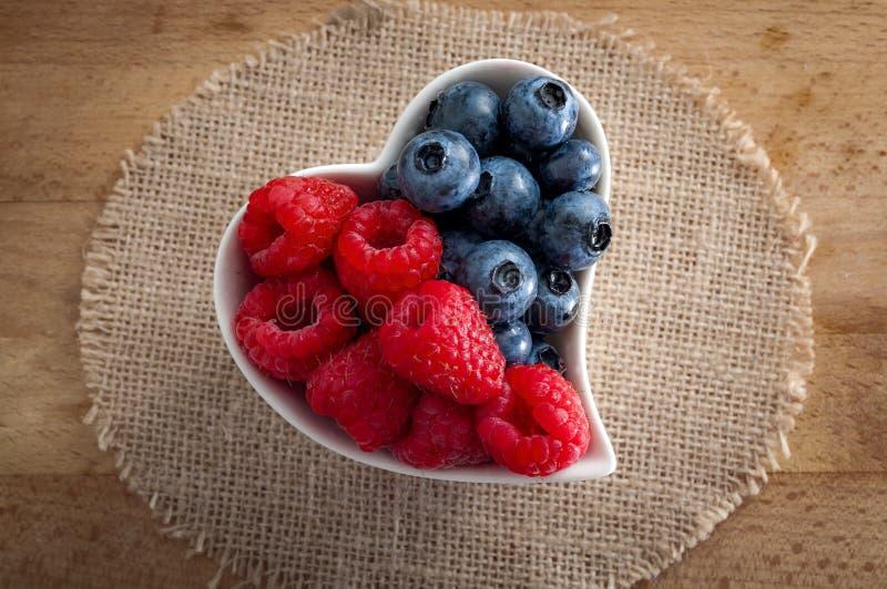 Os alimentos saudáveis e o bom conceito dos hábitos comendo com um coração deram forma à bacia branca de mirtilos e de framboesas imagens de stock