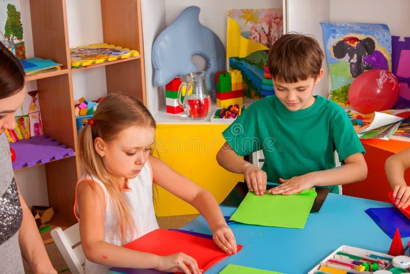 Os alunos com as tesouras nas crianças entregam o papel do corte imagens de stock