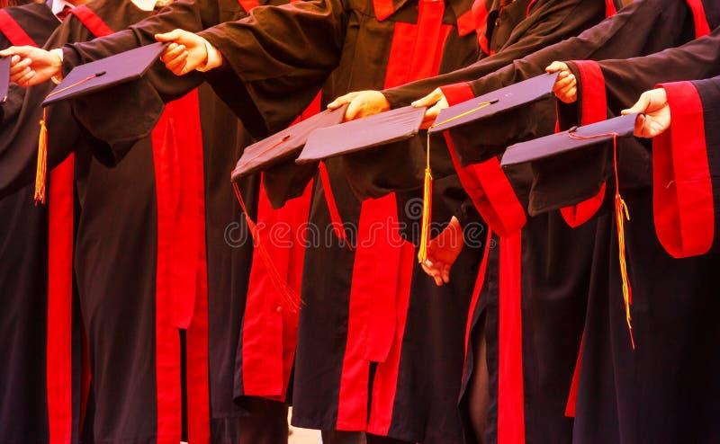 Os alunos diplomados guardam chapéus nas mãos na cerimônia do sucesso da graduação da universidade Felicitações no sucesso da edu fotografia de stock royalty free