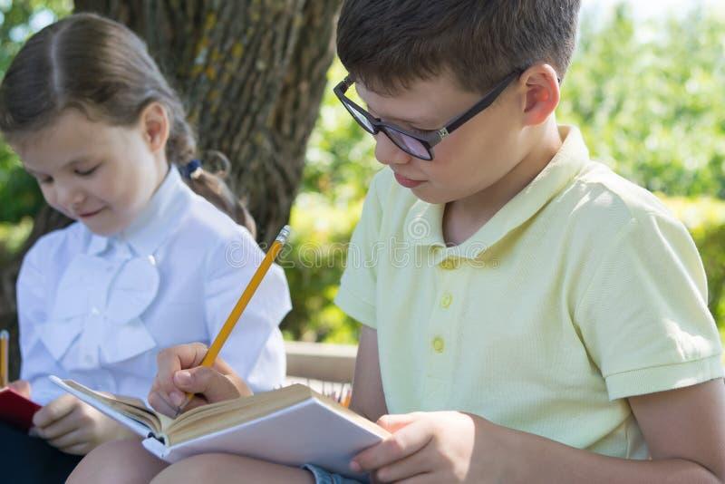 Os alunos menino e menina são contratados em uma lição exterior foto de stock