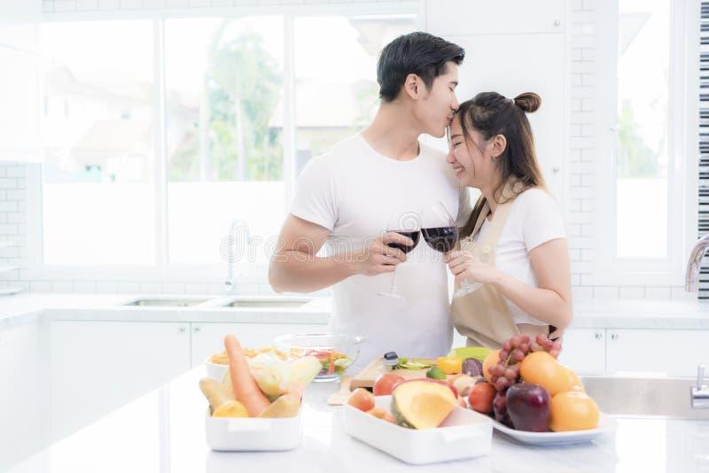 Os amantes asiáticos na cozinha, homem derem o beijo da testa à mulher quando vidros de vinho do tim-tim entre si fam?lia e conce foto de stock