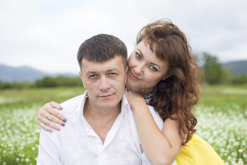 Os amantes encontram homens e mulheres em um campo de flor bonito fotos de stock royalty free