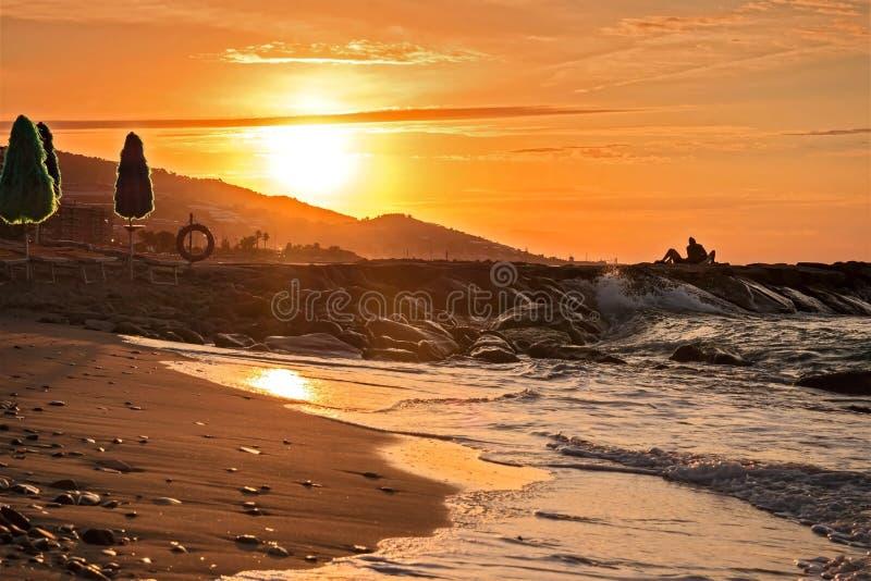 Os amantes encontram-se ao sunrice na praia O céu ao nascer do sol fotos de stock