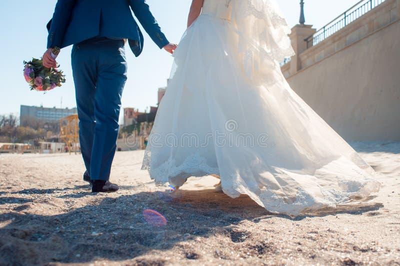 Os amantes estão correndo com mãos da posse na praia do mar fotos de stock