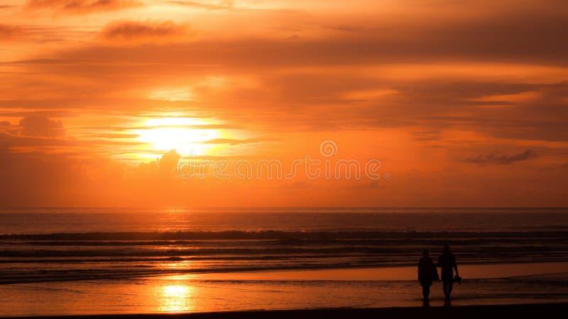 Os amantes que apreciam o por do sol do mar na praia foto de stock