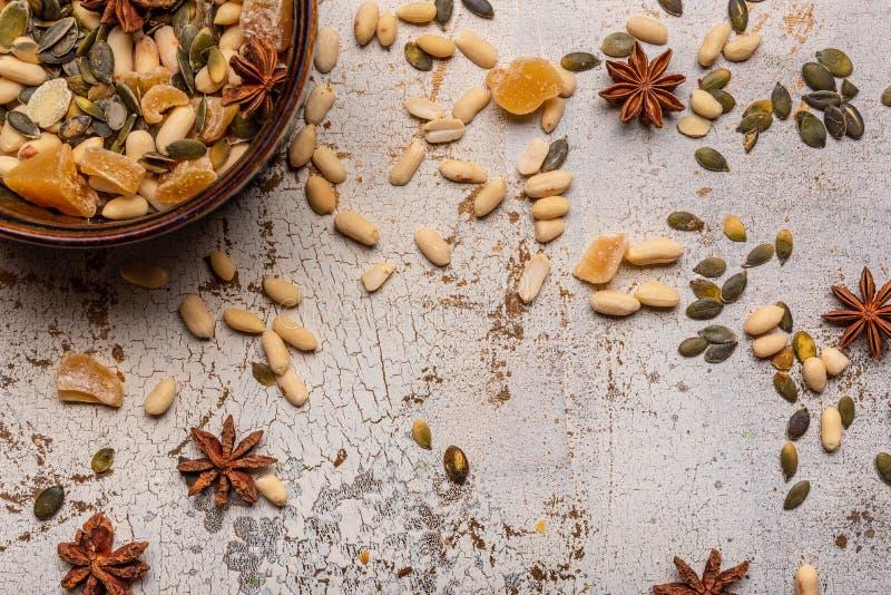 Os amendoins Anise Stars Candied Ginger e as sementes de abóbora em um prato de Brown no branco e no ouro racharam fundo Textured foto de stock royalty free