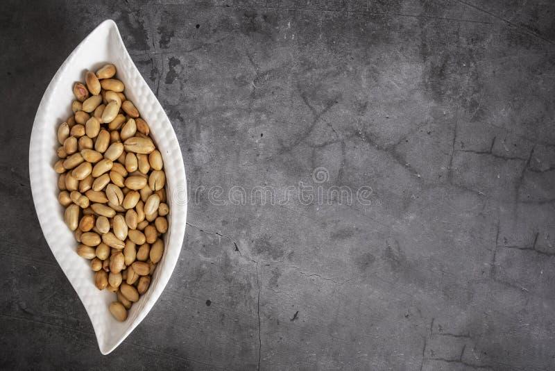 Os amendoins Roasted e salgados estão na placa branca da porcelana, vista superior dos amendoins, alinhada à esquerda para o text foto de stock royalty free
