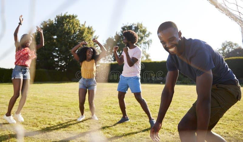 Os amigos adultos comemoram marcar o objetivo durante o jogo de futebol do divertimento imagem de stock royalty free