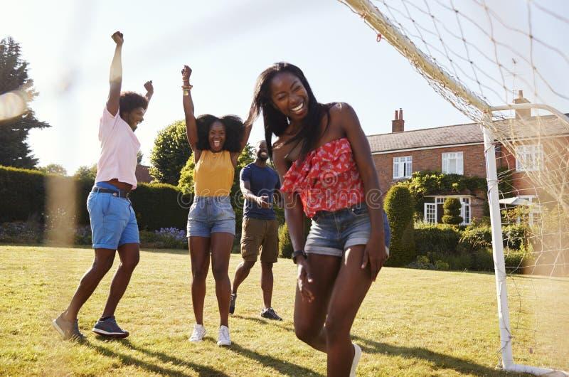 Os amigos adultos comemoram marcar o objetivo durante um jogo de futebol fotografia de stock royalty free