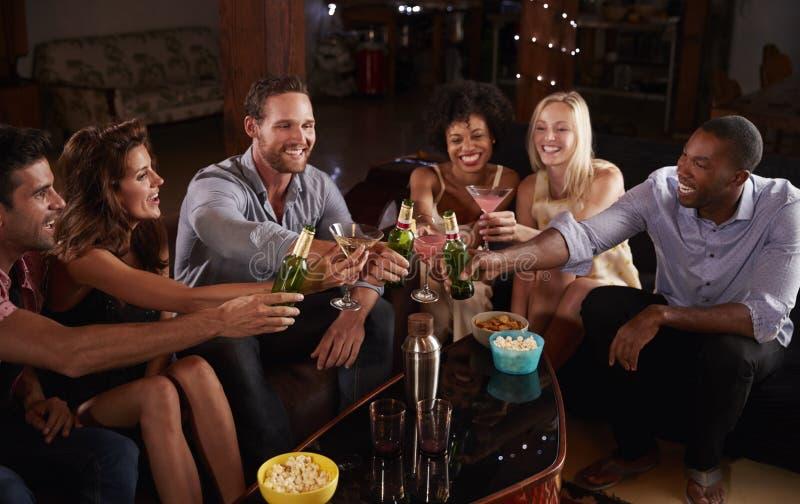 Os amigos adultos novos sentam-se fazendo um brinde em uma festa em casa imagem de stock