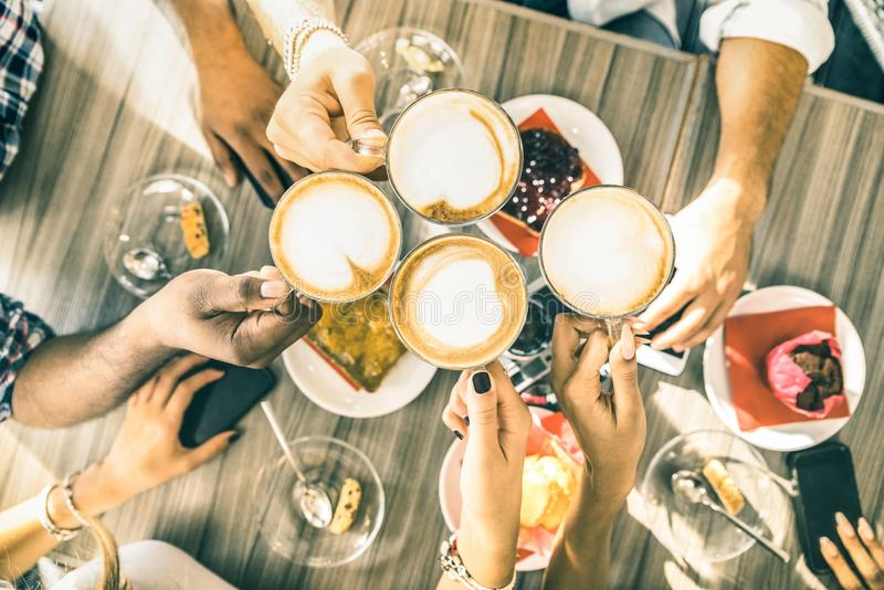 Os amigos agrupam o cappuccino bebendo no restaurante da barra de café fotografia de stock