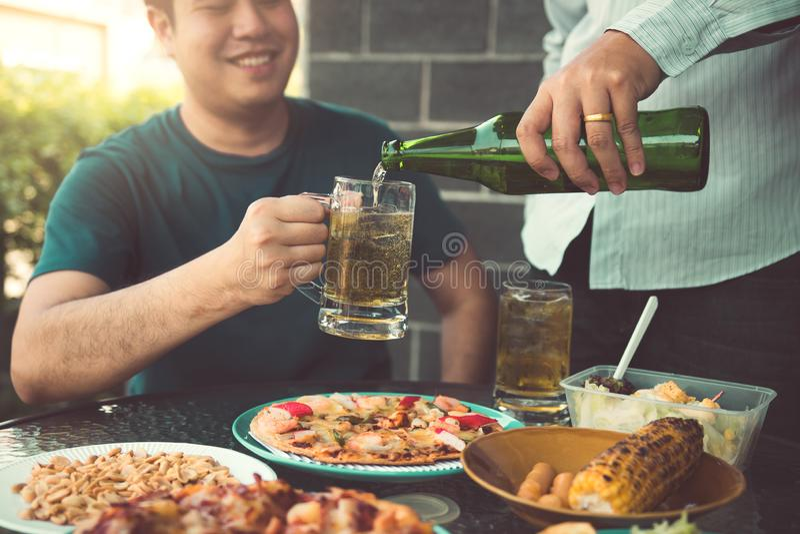 Os amigos asi?ticos est?o ajudando a derramar junto a cerveja na garrafa de seu s?cio e a ter o divertimento na celebra??o fotografia de stock