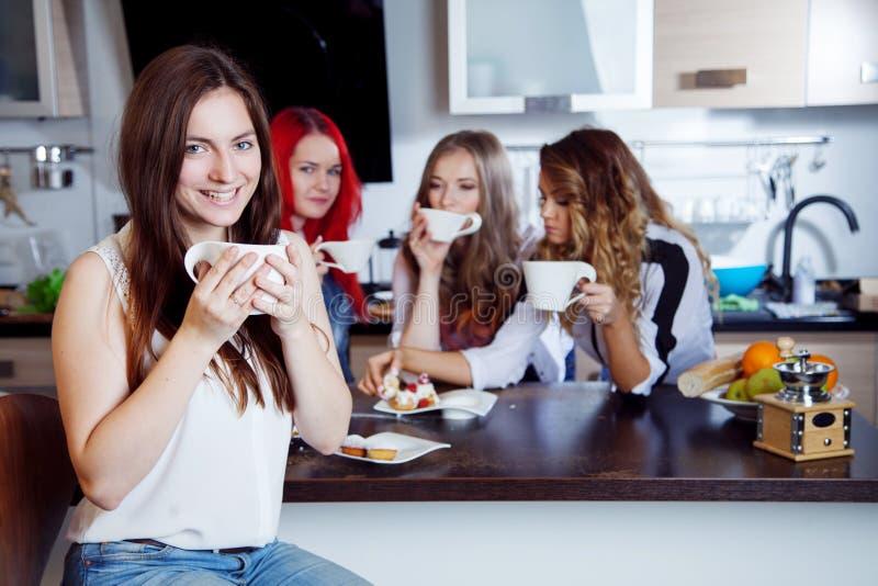 Os amigos bebem o chá e o café na cozinha, retrato da morena bonita nova no primeiro plano, mulher com copo branco fotos de stock royalty free