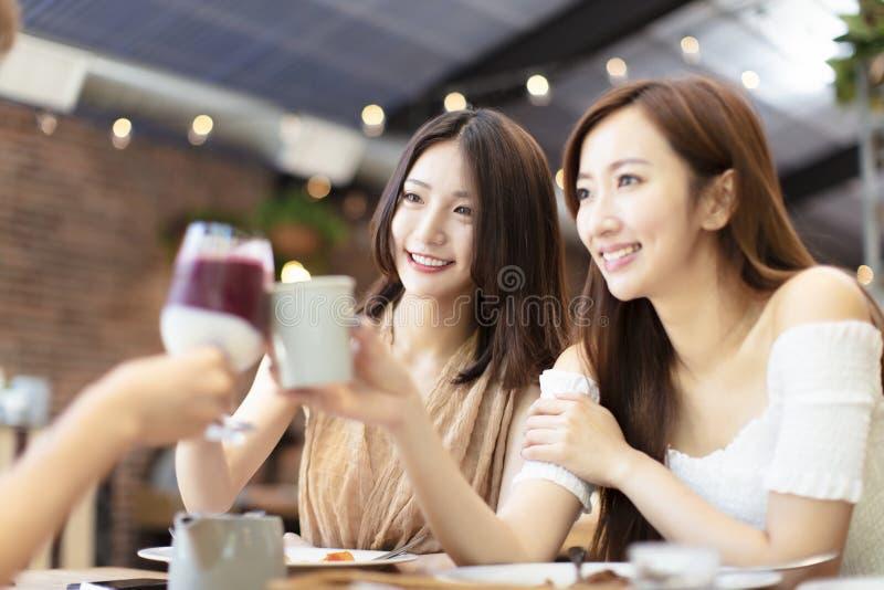 Os amigos comemoram com brinde e tim-tim no restaurante imagem de stock