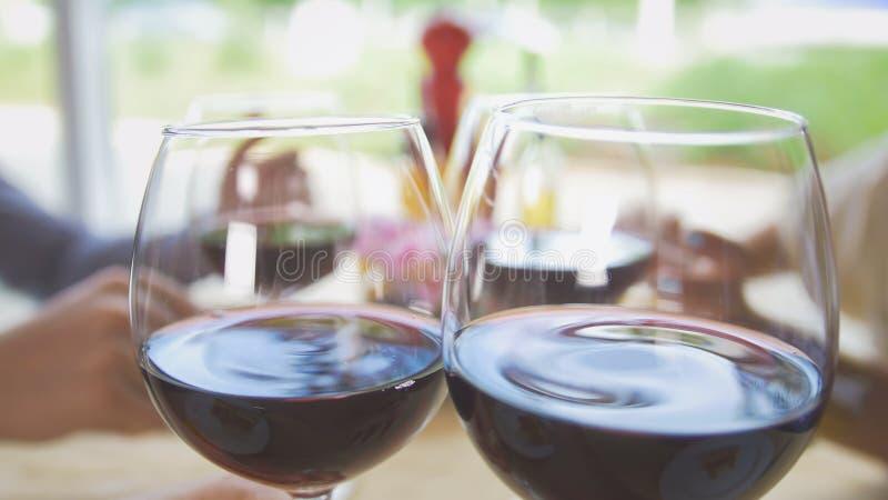 Os amigos comunicam-se no restaurante, o garçom trazem-nos wine imagens de stock