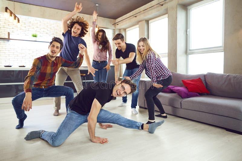 Os amigos dançam em um partido do ` s do estudante no apartamento imagens de stock