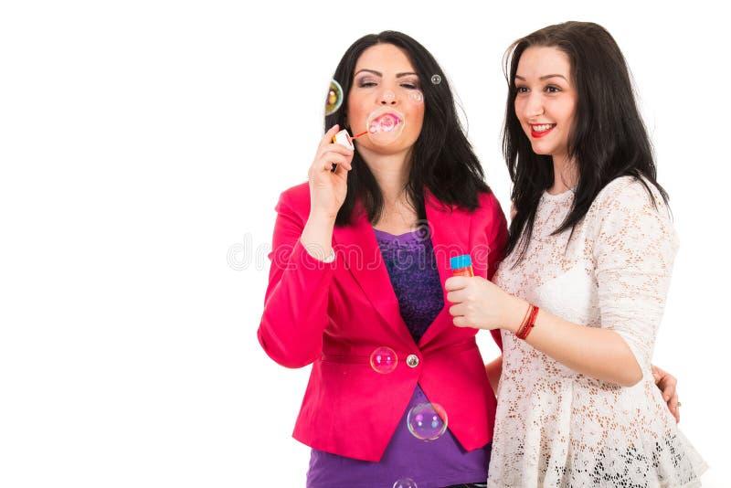 Os amigos das mulheres fundem borbulham para fora imagem de stock