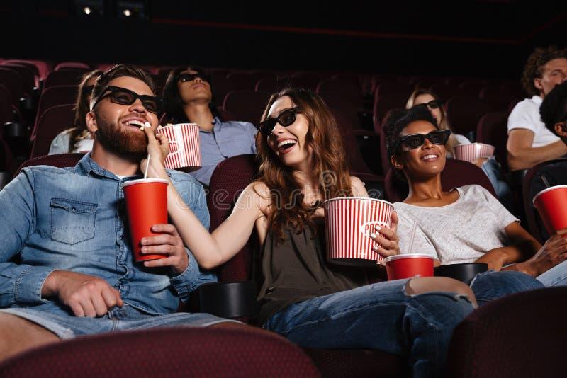 Os amigos de Hhappy que sentam-se no cinema olham o filme comer a pipoca imagens de stock royalty free