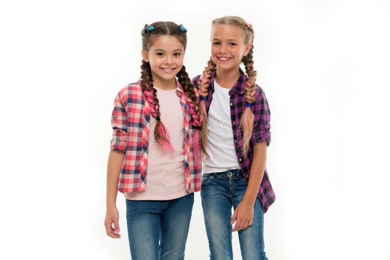 Os amigos de meninas vestem equipamentos similares têm o mesmo kanekalon do penteado trançam o fundo branco Equipamento do olhar  fotografia de stock