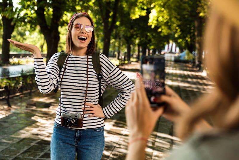 Os amigos de senhoras felizes que andam fora com trouxas tomam uma foto pelo telefone celular foto de stock