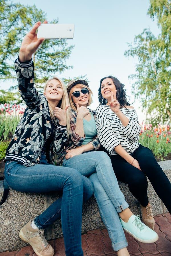 Os amigos do moderno fizerem o retrato da foto do selfie no parque quando por do sol do verão imagens de stock