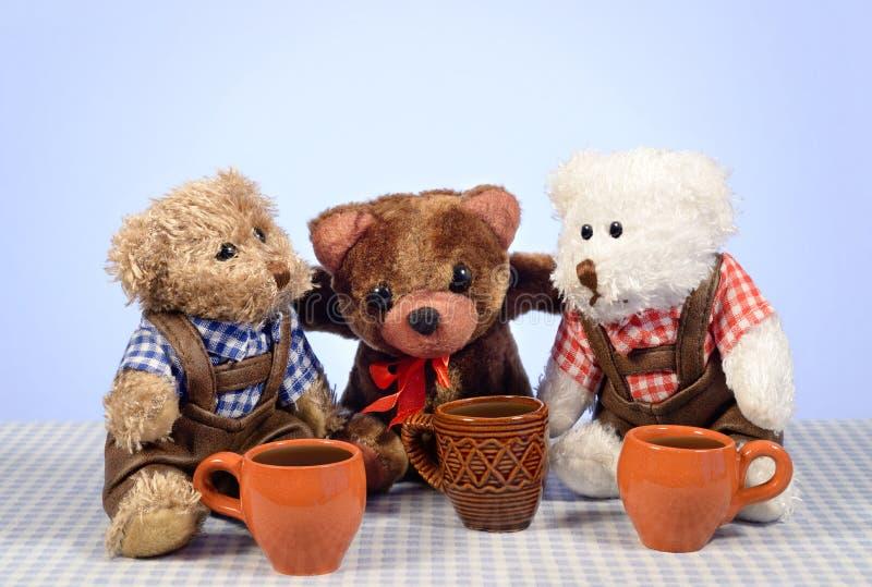 Os amigos do urso de peluche que sentam-se com canecas encheram bebidas quentes foto de stock royalty free