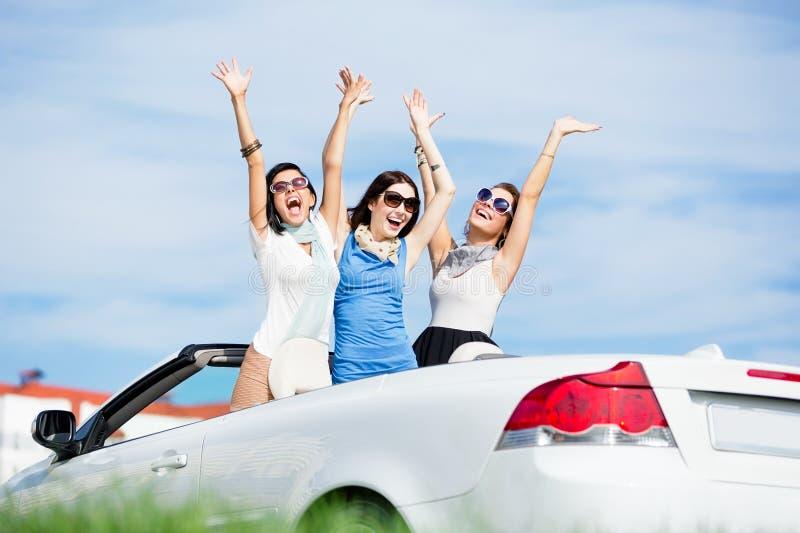 Os amigos estão no automóvel com mãos acima imagens de stock