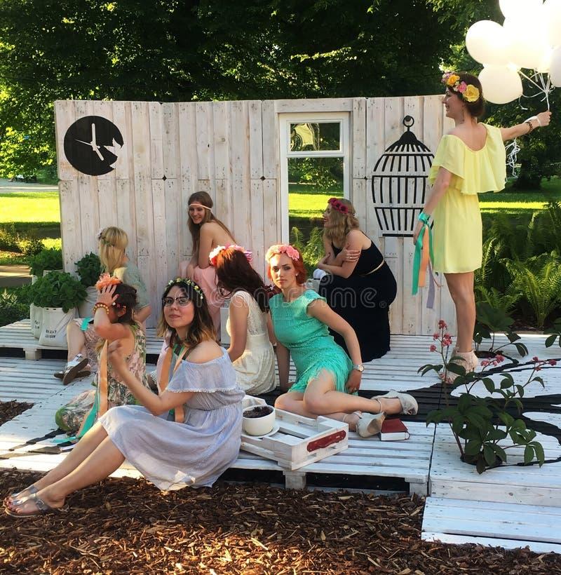 Os amigos fêmeas à moda com grinaldas da flor estão apreciando o galinha-partido ou o partido de chuveiro nupcial no parque imagens de stock royalty free