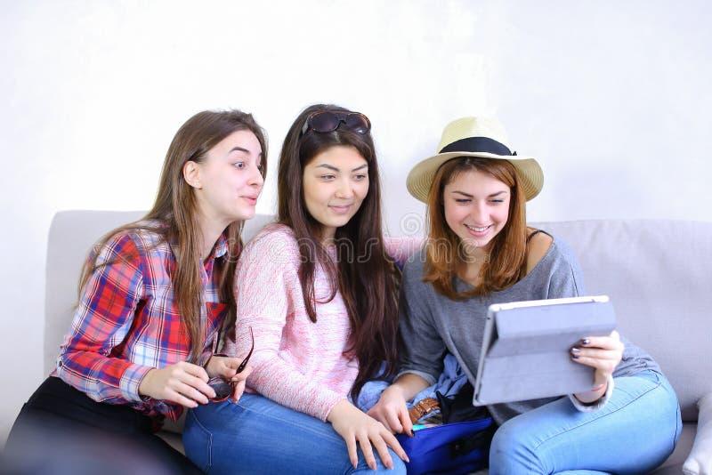 Os amigos fêmeas próximos usam a tabuleta e têm o divertimento, sentam-se no sofá no ro fotos de stock royalty free