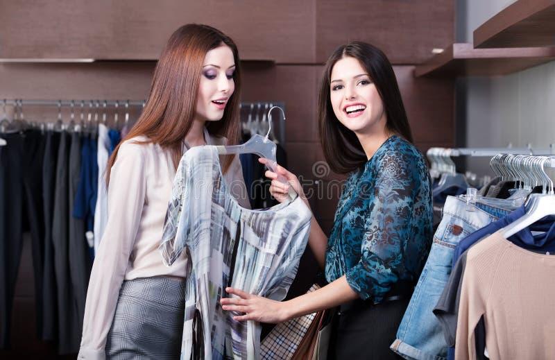 Os amigos fazem a compra e discutem um vestido imagens de stock royalty free