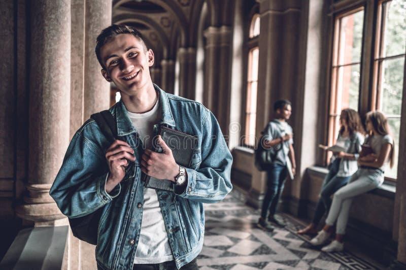 Os amigos fazem o divertimento da faculdade Retrato de um estudante novo considerável com seus amigos no fundo imagens de stock royalty free