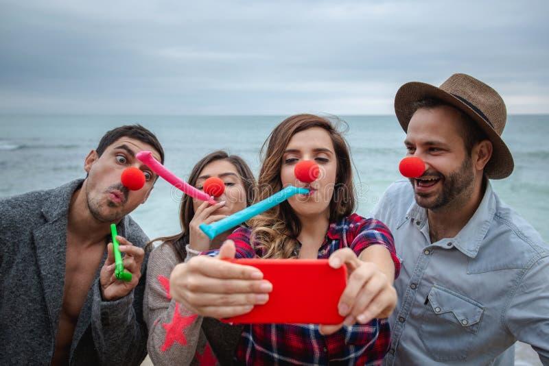 Os amigos fazem o selfie engraçado com smartphone vermelho imagem de stock royalty free