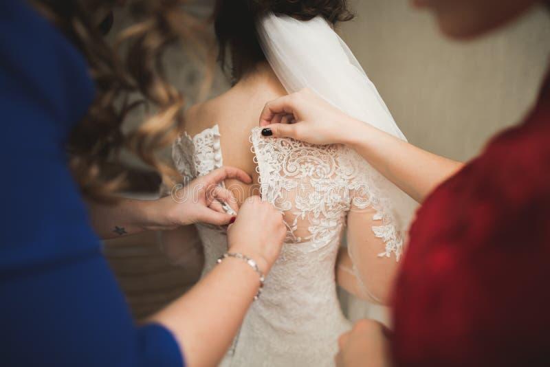 Os amigos felizes ajudam a noiva que prepara-se para seu dia do casamento na manhã imagens de stock
