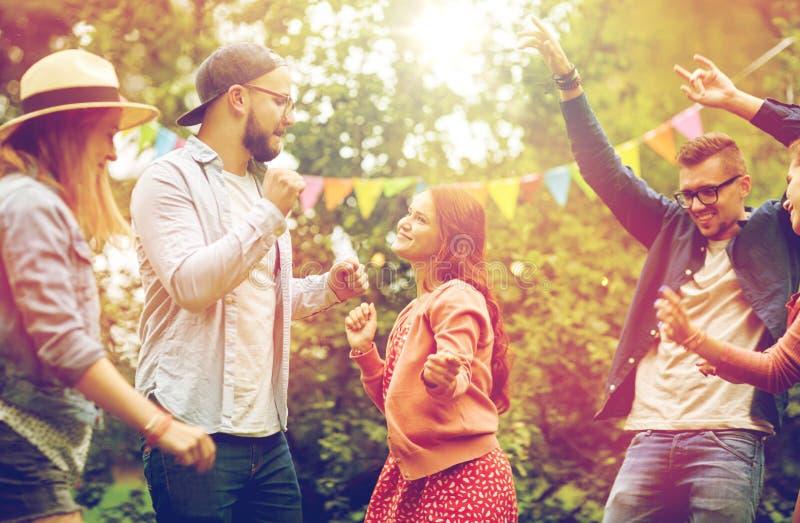 Os amigos felizes que dançam no verão party no jardim fotografia de stock