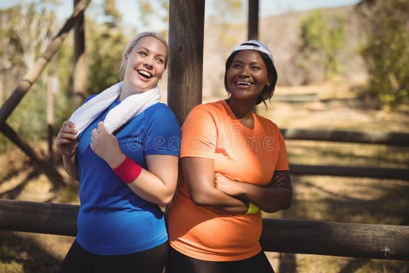 Os amigos felizes que estão com braços cruzaram-se durante o curso de obstáculo fotografia de stock royalty free