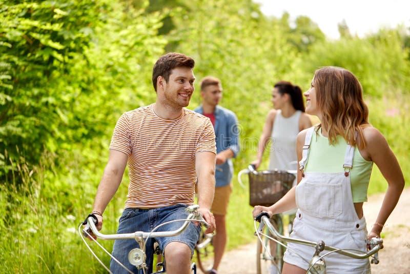Os amigos felizes que montam engrenagem fixa bicycles no verão foto de stock