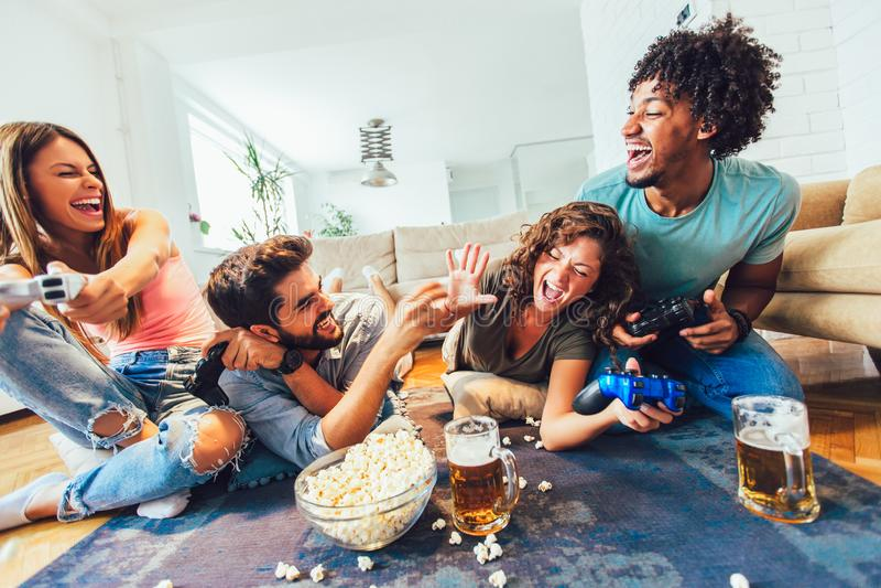 Os amigos jogam jogos de v?deo junto em casa, tendo o divertimento fotos de stock royalty free