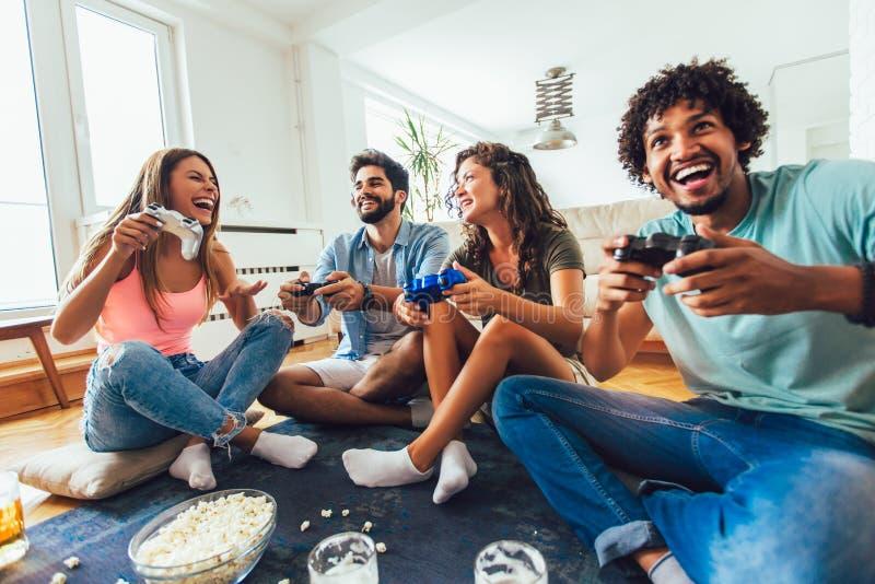 Os amigos jogam jogos de v?deo junto em casa, tendo o divertimento foto de stock